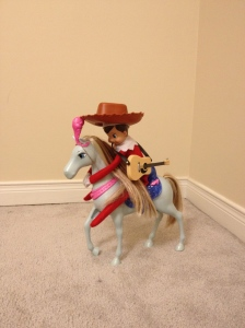 Blizzard riding Barbie's horse while wearing Woody's hat.