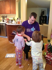 Aiden & Abby helping Dad open a present.