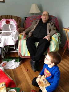 Grandpa looks on while Aiden opens a present.