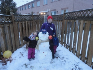 Melissa, Abby & Aiden posing with the family snowman