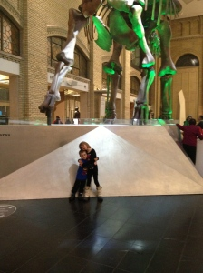 Abby & Aiden huggin each other underneath a large dinosaur