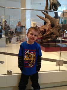 Aiden showing off his dinosaur face in front of a triceratops