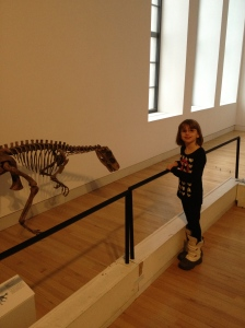 Abby looking at a small dinosaur that was tucked away down a hall