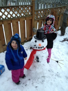 Aiden & Abby posing beside their snowman