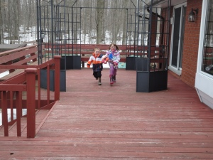 Aiden & Abby running with their windmills on the Allison's deck