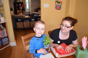 Aiden holding the plant that he gave tom Mom for Mother's Day
