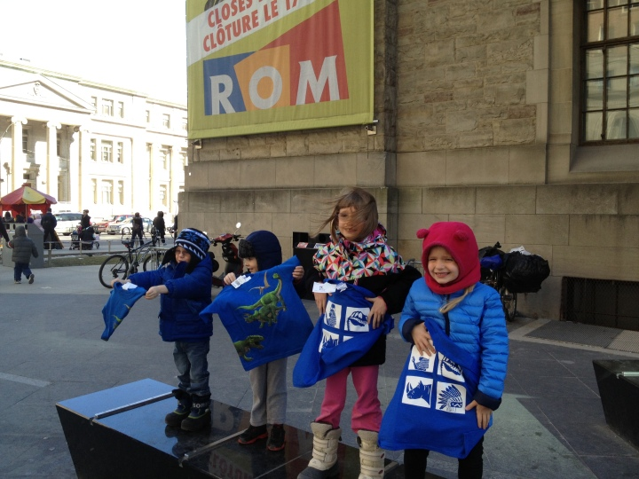 The kids holding the t-shirts outside the ROM