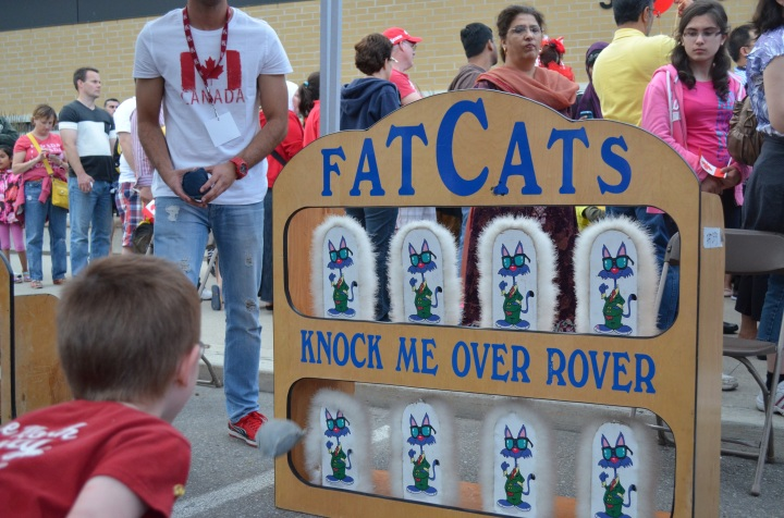 Aiden throwing bean bags at FatCats carnival game.