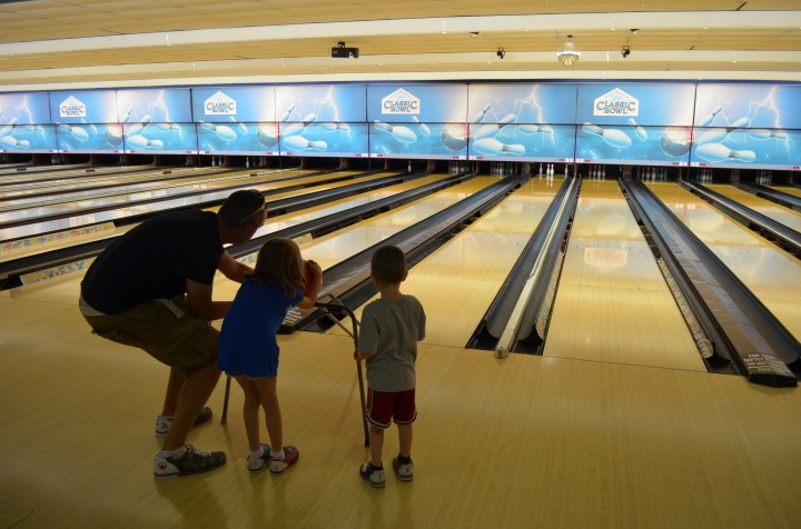 Dad helping the kids bowl
