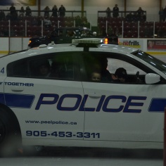 Aiden riding in the police car at a fundraiser