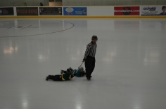 Aiden being dragged around the ice by his stick