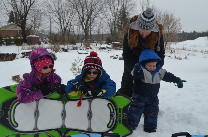 Abby, Aiden, Macklan and Aunt Julie outside playing in the snow