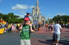 Aiden riding Dad's shoulders in front of Cinderella's Castle