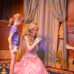 Abby getting Princess Aurora to sign her book while Aiden waits patiently