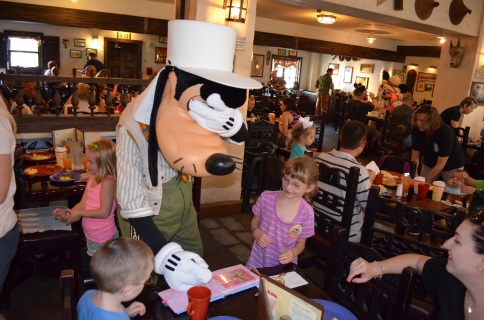 Goofy covering his eyes while signing the kids autograph book