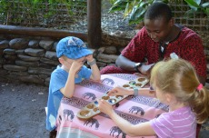 Kids playing Mancala with Volunteer Student