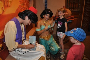 Jasmine and Aladdin signing the kids autograph book