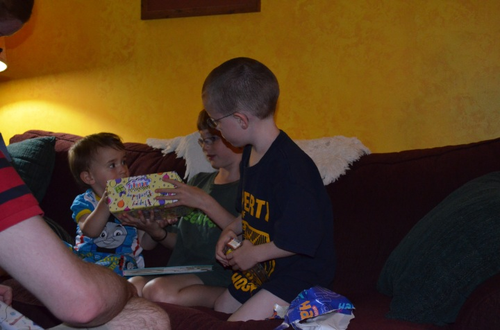 Abby and Aiden helping Macklan open his birthday presents.
