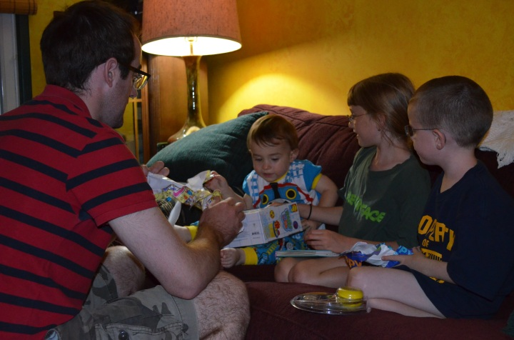 Aiden, Abby, and Uncle Rob look on as Macklan opens his birthday presents.