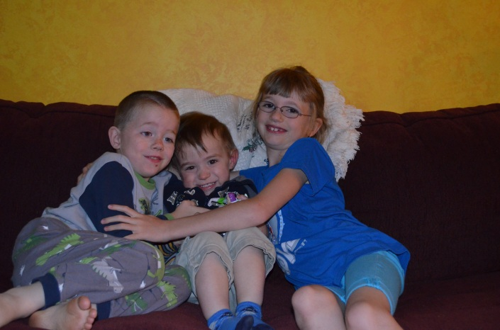Aiden and Abby hugging their cousin Macklan.