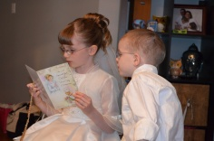 Abby reading one of her cards with Aiden looking on