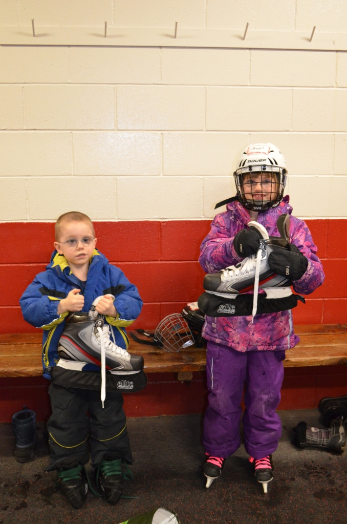 Abby and Aiden holding Daddy's skates.