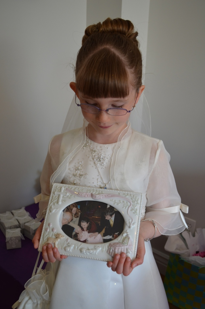 Abby holding a picture of when she was baptized.
