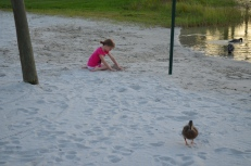Abby building a sand castle with a duck