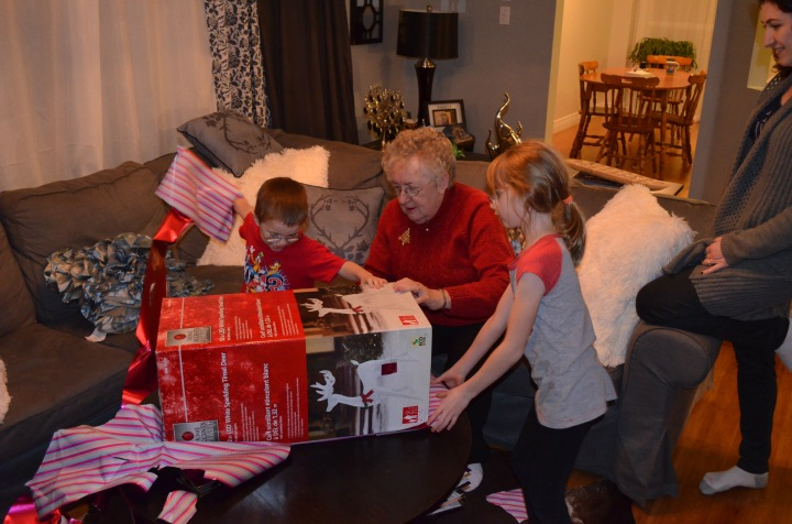 Kids helping Mama open her gift