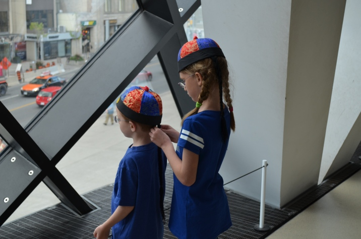 Abby fixing the back of Aiden's hat as they look out onto Bloor St.
