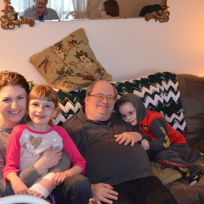 Abby sitting on Mommy and Aiden snuggling with Grandpa
