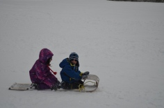 Abby and AIden riding down the hill on their toboggan