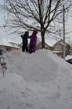 Abby and Aiden standing on the snow bank on our front yard