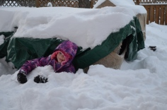 Abby making a fort using the patio furniture in the backyard