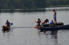 Stephanie G. shooting water at Jordan from the dock. Aaron is in other canoe. Lucas is on the dock.