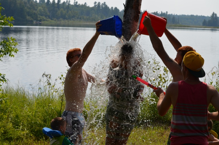 Lucas, Philip and Jordan dumping water onto Stephanie G. who is taped to the tree.