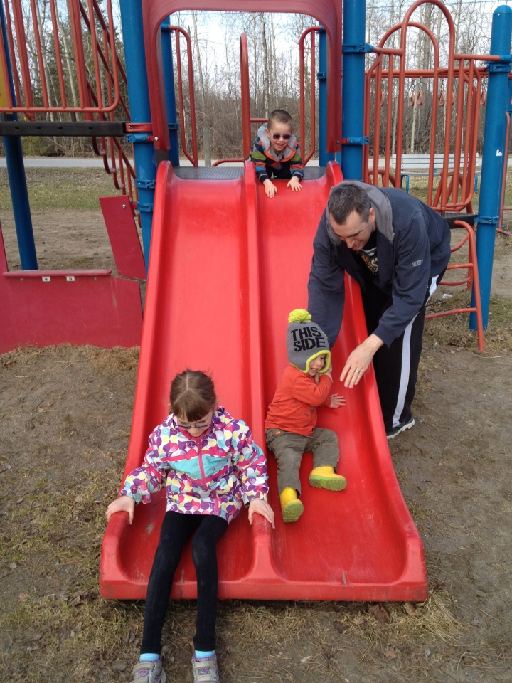 Peter helping Macklan down the slide while Aiden looks on and Abby slides beside him.