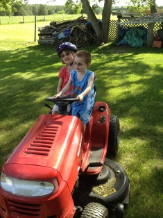 Abby and Aiden sitting on Papa's riding lawn mower
