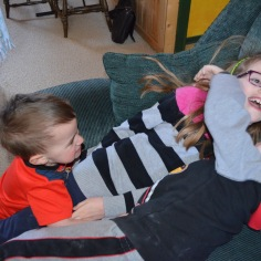 Abby, Macklan and Aiden wrestling on the couch.