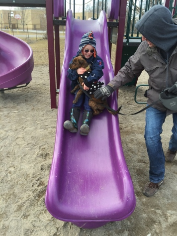Aiden going down the slide with Marley at the park on Easter.