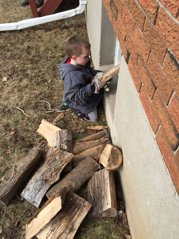 Aiden helping his Dad and Papa throw in the wood.