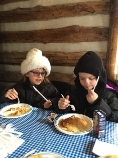 Abby and Ava eating pancakes at the Maple Syrup Festival at the Bradley Museum.