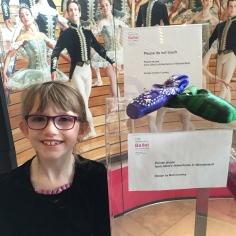 Abby beside Alice's slipper at the ballet.