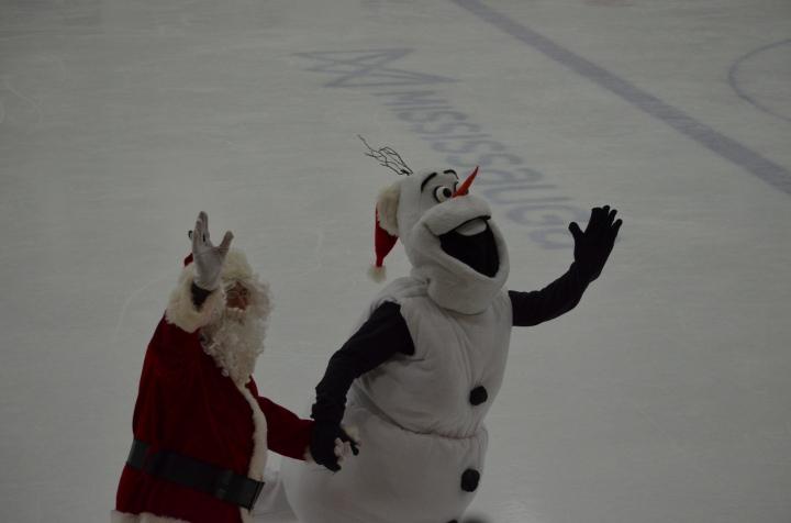 Santa and Olaf skating hand in hand.