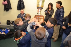 Abby and the boys holding up the championship trophy in the dressing room after the game.
