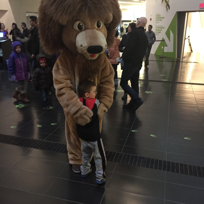 Aiden hugging the lion at the ROM