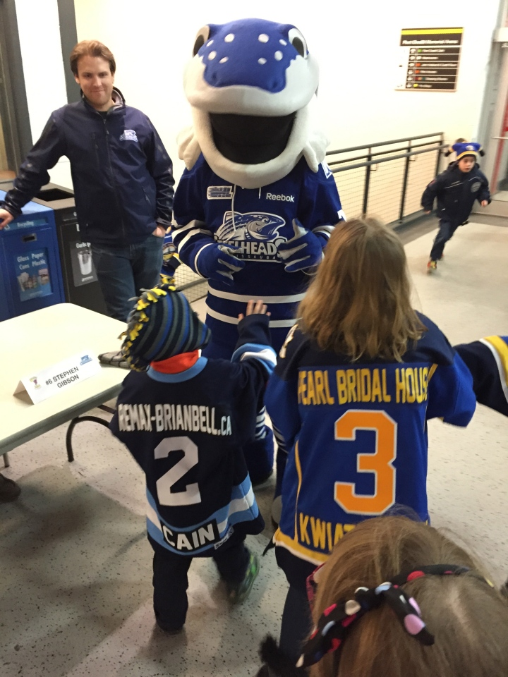 Aiden and Abby high-fiving Sauga at PCHA Coaches night.
