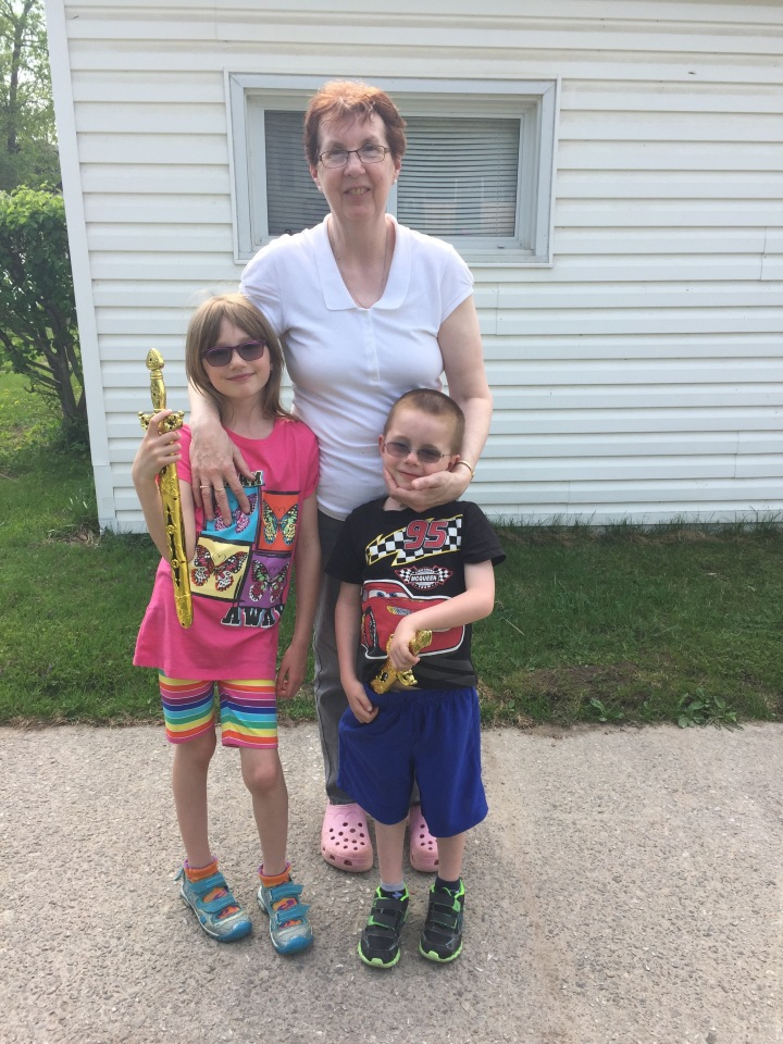 Abby and Aiden with Grandma holding the swords that Grandma gave them