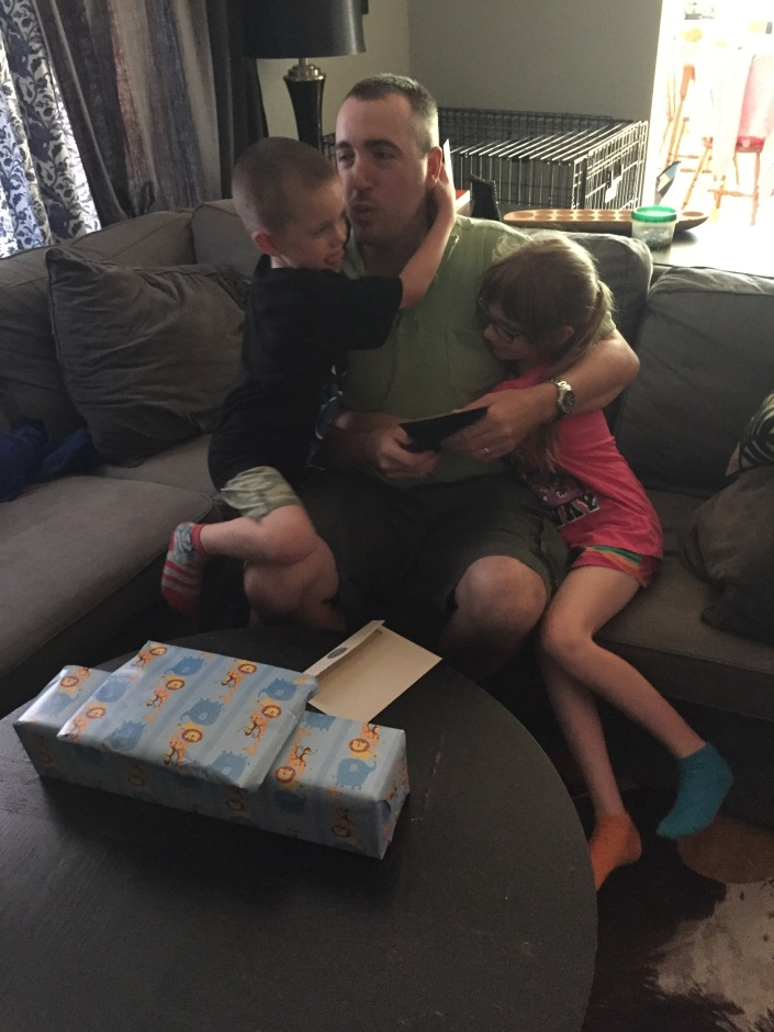 Peter getting hugs and kisses from Abby and Aiden after opening their gifts from school.