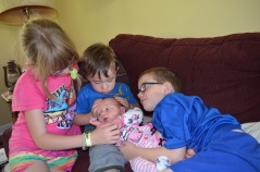 Macklan holding his little sister Eva with Abby and Aiden looking on.